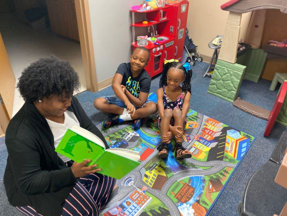 Kiara Tookes-Williams reads a story to a staff member's children