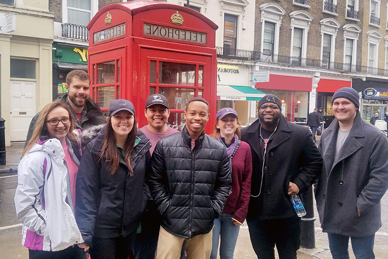 A group of students standing in front of an iconic red phone booth during a trip to London