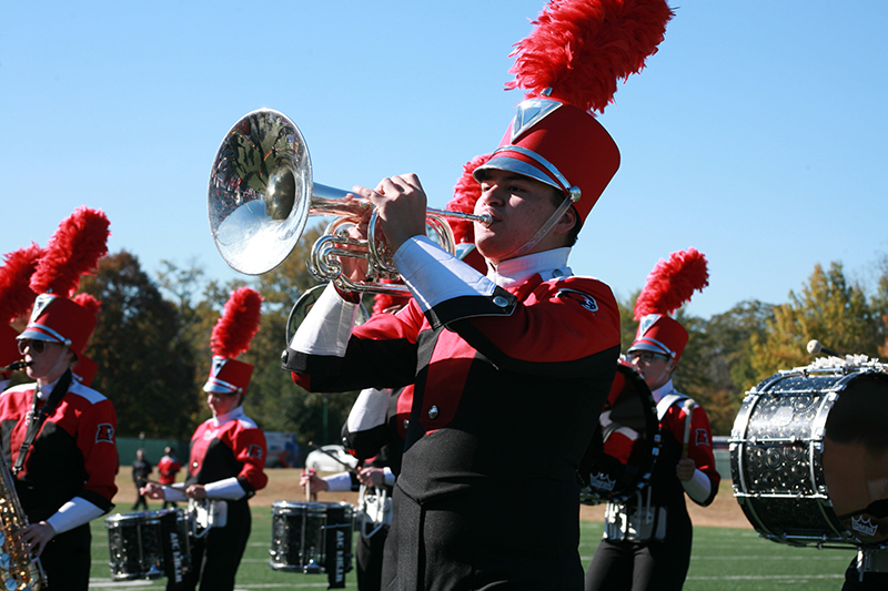 Marching b和 member playing a cornet during a football halftime show