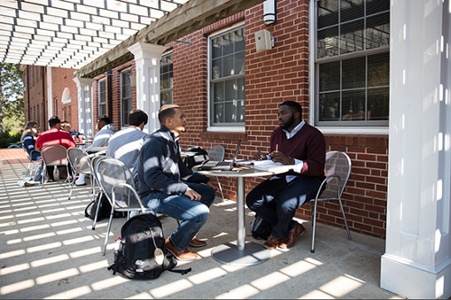 Two students sitting at a table 和 studying underneath the pergola on the porch of Turner Hall
